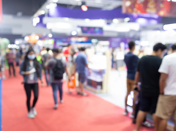 Blurred group of people walking through event booths.