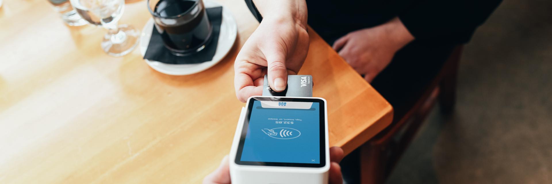 woman using a visa credit card at the coffee shop