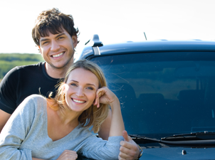 couple smiling in front of car