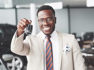 man holding out car keys
